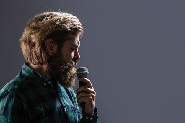 Mężczyzna z brodą, trzymając mikrofon i śpiewając. brodaty mężczyzna w karaoke śpiewa