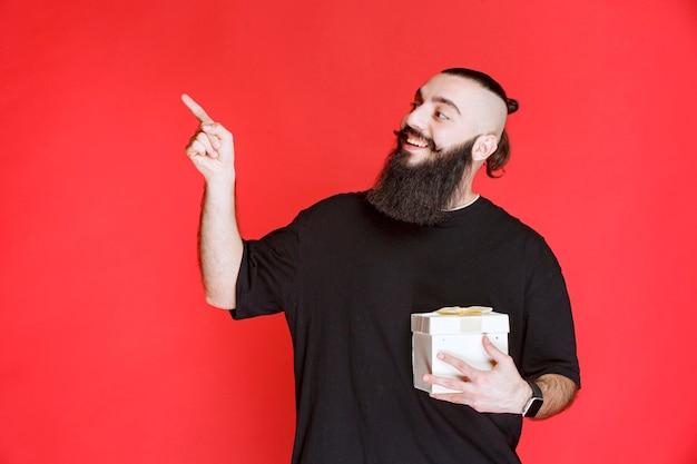 Mężczyzna z brodą, trzymający białe pudełko i wskazujący na kogoś.