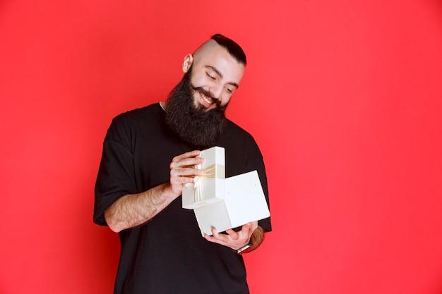 Mężczyzna z brodą, trzymający białe pudełko upominkowe i otwierający je z podekscytowaniem.