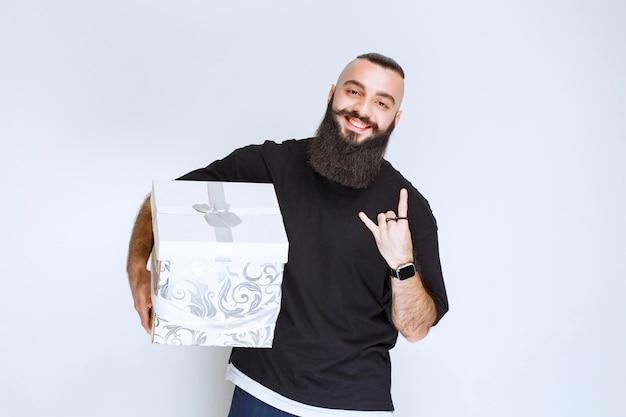 Mężczyzna z brodą trzymający biało-niebieskie pudełko i czujący się sukcesem.