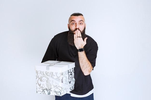 Mężczyzna z brodą trzymający biało-niebieskie pudełko z prezentami, wskazując ustami i prosząc o ciszę.