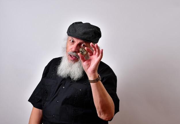 Mężczyzna z brodą trzymający bitcoin i patrząc na to