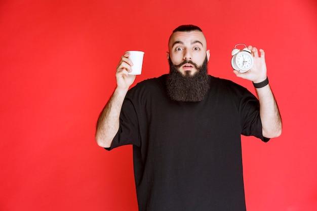 Mężczyzna z brodą, trzymający budzik i filiżankę kawy.