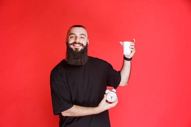 Mężczyzna z brodą, trzymający budzik i mający filiżankę kawy.