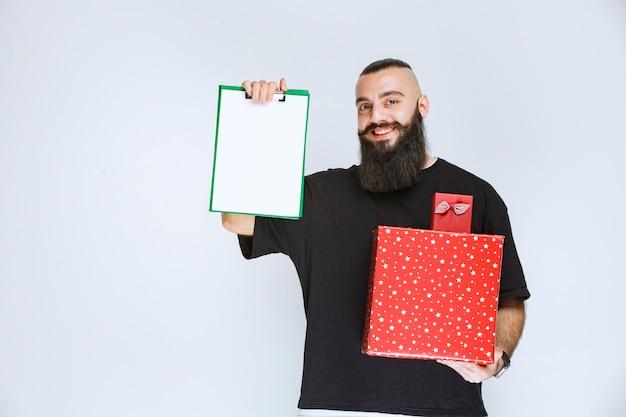 Mężczyzna z brodą trzymający czerwone pudełka na prezenty i proszący o podpis na liście dostaw.
