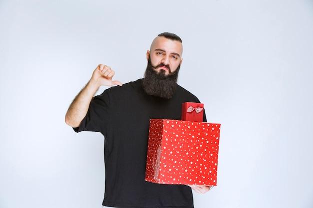 Mężczyzna z brodą, trzymający czerwone pudełka na prezenty i wskazujący zadek z bladą twarzą.