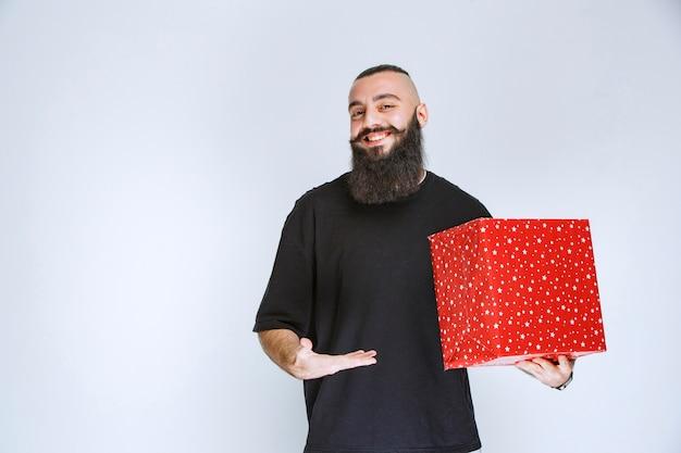 Mężczyzna z brodą trzymający czerwone pudełko na prezent