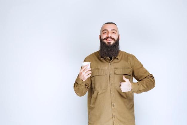 Mężczyzna z brodą trzymający filiżankę kawy i cieszący się smakiem.