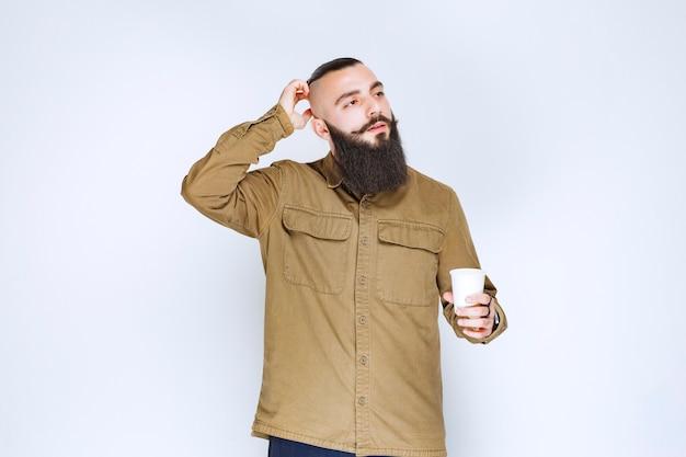 Mężczyzna z brodą trzymający filiżankę kawy i myślący.