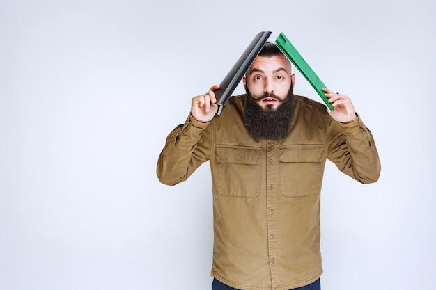 Mężczyzna z brodą trzymający folder nad głową, aby chronić przed deszczem.