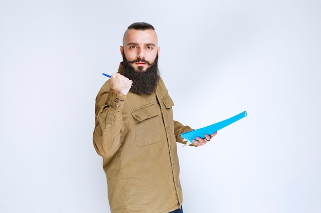 Mężczyzna z brodą trzymający folder raportu i wskazujący na swojego kolegę.