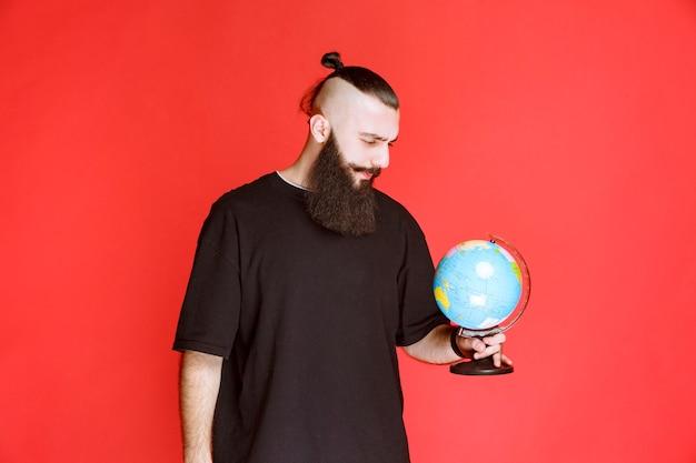 Mężczyzna z brodą trzymający kulę ziemską i szukający nad nią miejsc.