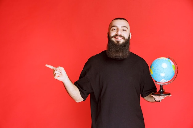 Mężczyzna z brodą, trzymający kulę ziemską i wskazujący gdzieś.