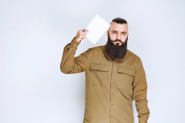 Mężczyzna z brodą trzymający papier do quizu, wyglądający na zdezorientowanego i zamyślonego.