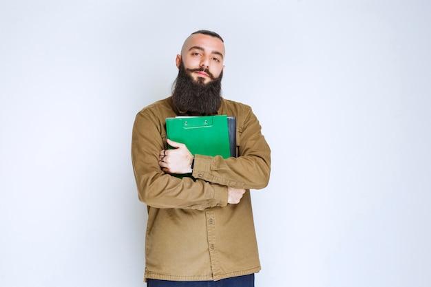 Mężczyzna z brodą trzymający swoją listę raportów i czekający z ufnością.
