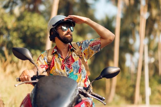 Mężczyzna z brodą w kolorowym tropikalnym koszulowym obsiadaniu na motocyklu