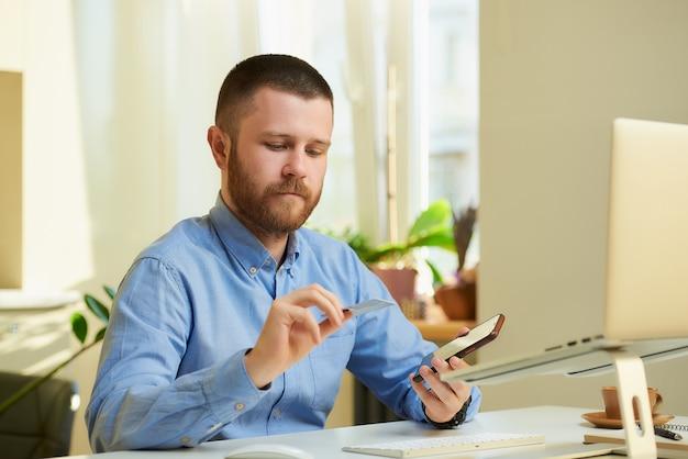 Mężczyzna z brodą w koszuli przewracający kartę kredytową w pobliżu komputera w domu.