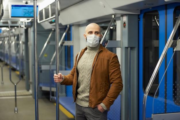 Mężczyzna z brodą w masce medycznej, aby uniknąć rozprzestrzeniania się covid-19, jedzie wagonem metra i trzyma poręcz