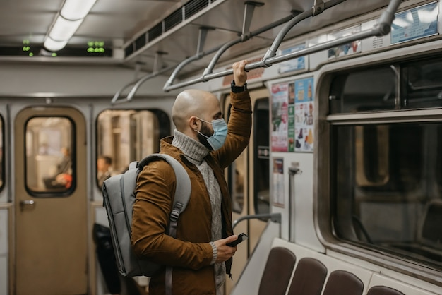 Mężczyzna z brodą w masce na twarz, aby uniknąć rozprzestrzeniania się koronawirusa, patrzy przez okno w wagonie metra