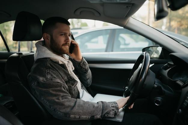 Mężczyzna z brodą w przypadkowych ubraniach robi interesy na smartfonie w samochodzie, na kolanach leży laptop. facet zatrzymał samochód, aby natychmiast zdalnie rozwiązać zadania w pracy w dystansie społecznym