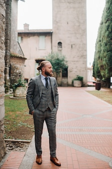 Mężczyzna z brodą w surowym szarym trzyczęściowym garniturze z krawatem na starym mieście w sirmione, stylowy mężczyzna w szarym garniturze we włoszech.