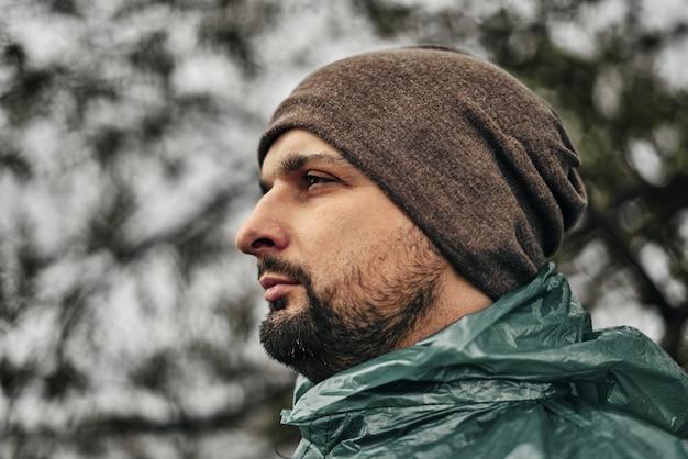 Mężczyzna z brodą w zielonym płaszczu przeciwdeszczowym i kapeluszu.