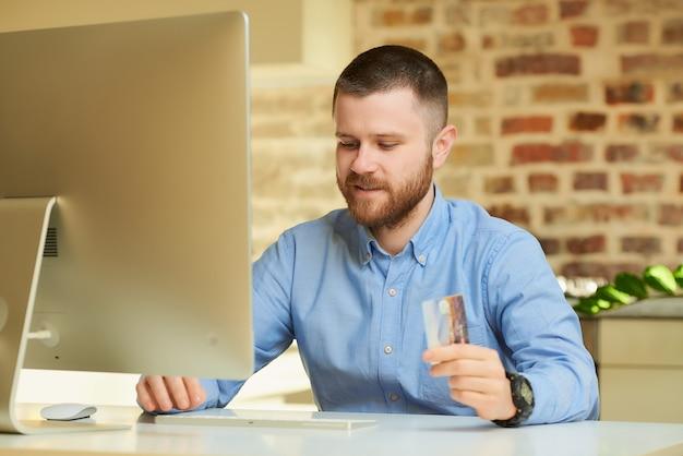 Mężczyzna z brodą wpisuje dane karty kredytowej, aby robić zakupy online w domu
