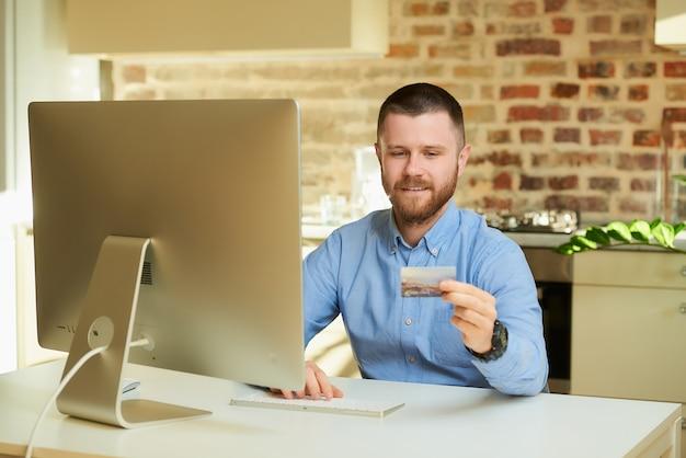 Mężczyzna z brodą wpisuje numer karty kredytowej, aby robić zakupy online w domu