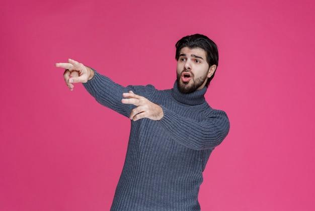 Mężczyzna z brodą, wskazujący na coś lub przedstawiający kogoś.