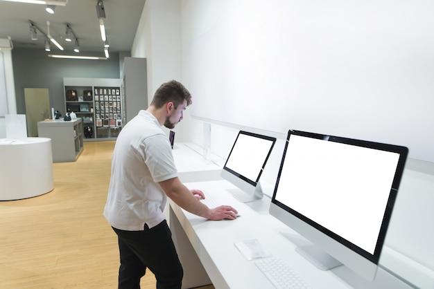 Mężczyzna z brodą wybiera komputer w sklepie elektronicznym.