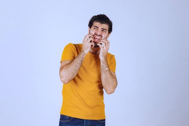 Mężczyzna z brodą wygląda na przestraszonego i przestraszonego