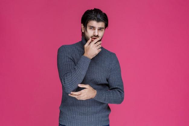 Mężczyzna z brodą wygląda na zagubionego i zamyślonego.