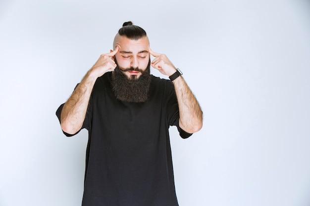 Mężczyzna z brodą wygląda na zamyślonego i marzy.