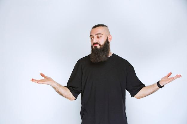 Mężczyzna z brodą wygląda na zdezorientowanego i wahającego się.