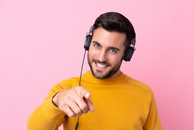 Mężczyzna z brody słuchającą muzyką nad odosobnioną ścianą