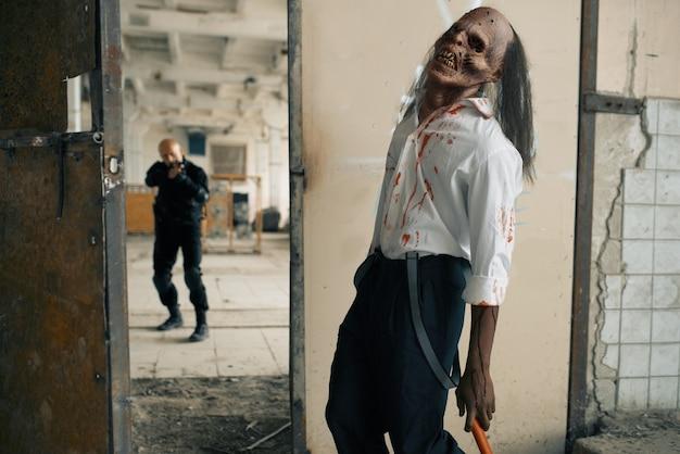 Mężczyzna z bronią palną walczy z nieumarłym zombie, koszmar w opuszczonej fabryce. horror w mieście, przerażające czołgi, apokalipsa końca świata, krwawy zły potwór