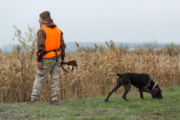 Mężczyzna z bronią w rękach i pomarańczową kamizelką na bażanta poluje w zalesionym terenie przy pochmurnej pogodzie.
