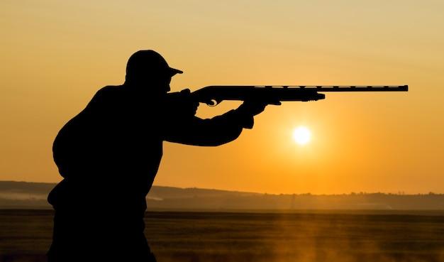 Mężczyzna z bronią w ręku na polowaniu na bażanta w zalesionym terenie przy pochmurnej pogodzie
