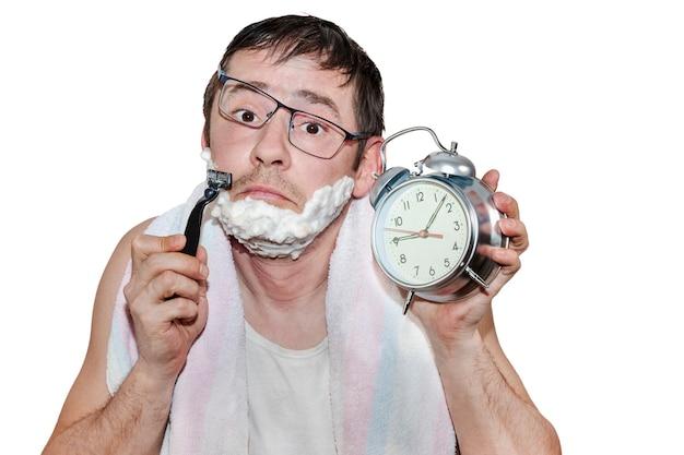 Mężczyzna z budzikiem rano zasnął i zrywa się na nogi przekrzywione okulary