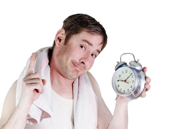 Mężczyzna z budzikiem spał rano. ręcznik na ramiona. zabawny wyraz twarzy. palec wskazujący uniesiony do góry. na białym tle.