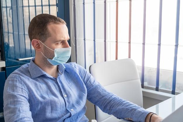 Mężczyzna z chirurgiczną maską przyglądającą jego domowego okno. koncepcja kwarantanny.