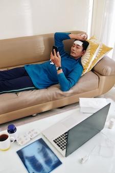 Mężczyzna z chłodną gorączką na czole leżący na kanapie i czytający zalecenia swojego lekarza na smartfonie