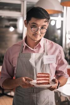 Mężczyzna z ciastem. ciemnowłosy przystojny mężczyzna w okularach, trzymając tort ze swojej kawiarni