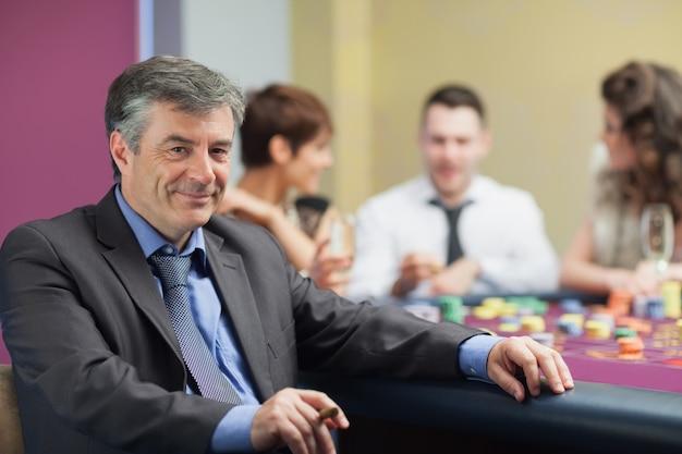 Mężczyzna z cygarem bierze przerwę od ruleta stołu