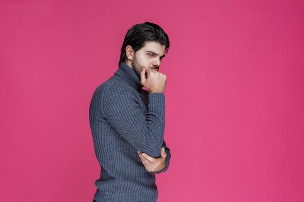 Mężczyzna z czarną brodą wygląda na wyczerpanego i znudzonego.