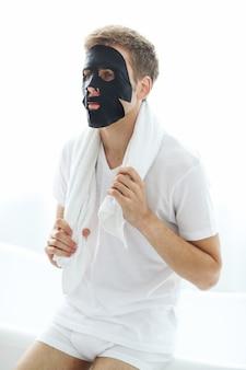 Mężczyzna z czarną maską na twarz, węglem oczyszczającym skórę. koncepcja piękna