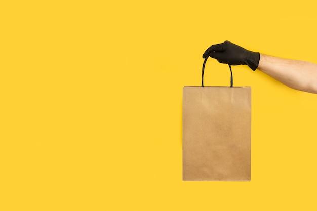 Mężczyzna z czarną rękawicą chirurgiczną trzymający brązową papierową torbę na żółtym tle