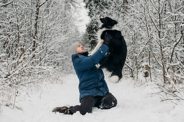 Mężczyzna z czarno-białym psem rasy border collie w śniegu