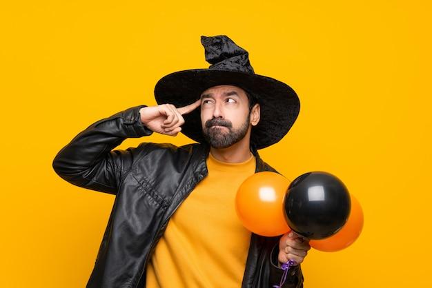 Mężczyzna z czarownica kapeluszem trzyma czarnych i pomarańczowych lotniczych balony dla halloween przyjęcia ma wątpliwości i główkowanie