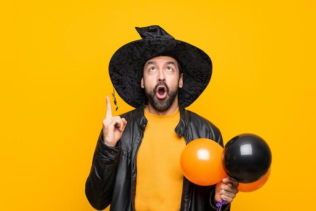 Mężczyzna z czarownica kapeluszem trzyma czarnych i pomarańczowych lotniczych balony dla halloween przyjęcia wskazuje w górę i zaskakujący